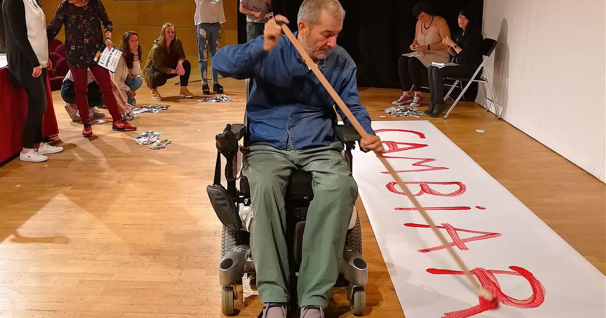"""José Antonio Nóvoa pintando la palabra """"cambiar"""" sobre una pancarta en el suelo"""