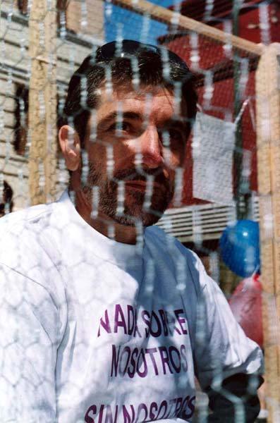 Activista dentro de la jaula con una camiseta con el lema 'Nada sobre nosotros sin nosotros'